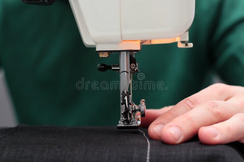 Les processus de coudre Linum sur la machine à coudre cousent la machine à coudre Linum de mains du ` s de femmes machine à coudr photo stock