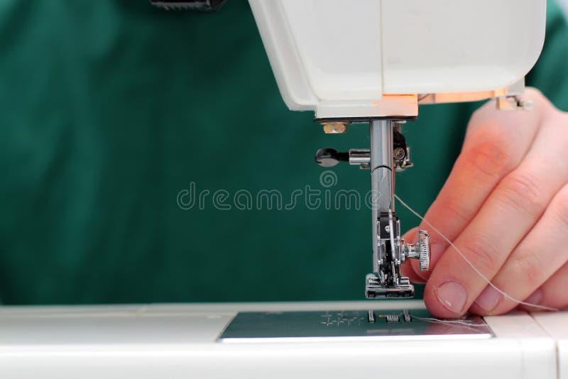 Les processus de coudre Linum sur la machine à coudre cousent la machine à coudre Linum de mains du ` s de femmes machine à coudr photographie stock