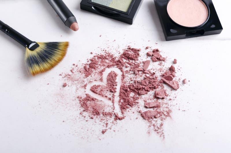 Les produits de maquillage, écrasés pour rougir poudre, forme de coeur est un symbole de maquillage d'amour photos stock