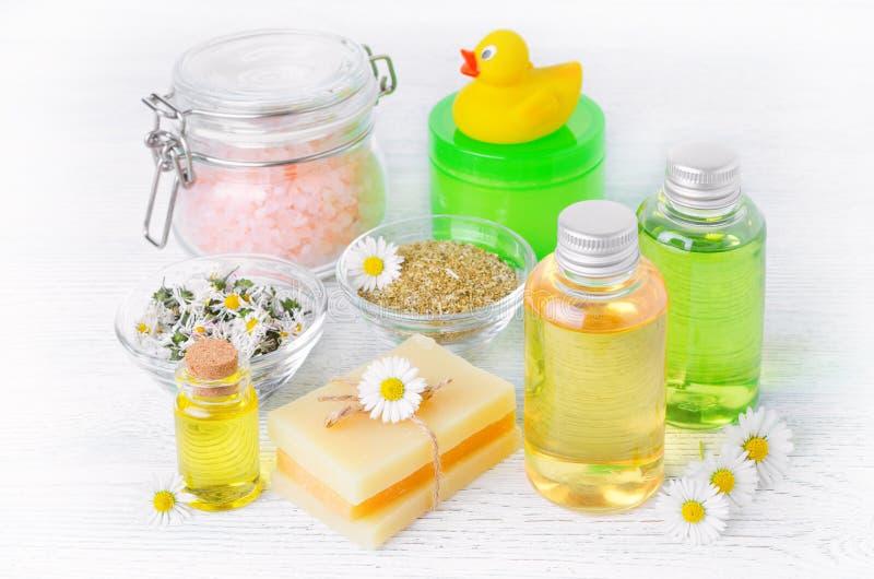Les produits naturels de soin de bébé avec la camomille huilent, les fleurs extrait, le savon, le sel, la crème et le shampooing photos libres de droits