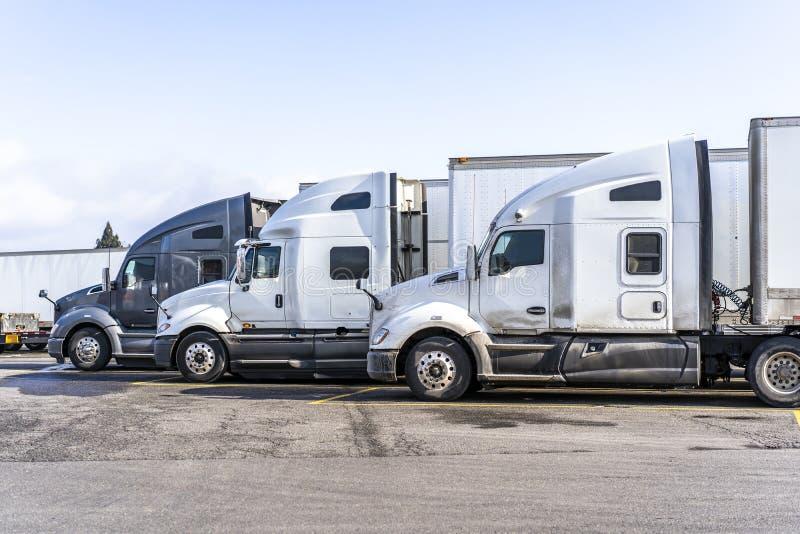 Les profils de grands camions d'installations semi avec semi des remorques se tiennent sur le parking large du relais routier photo libre de droits