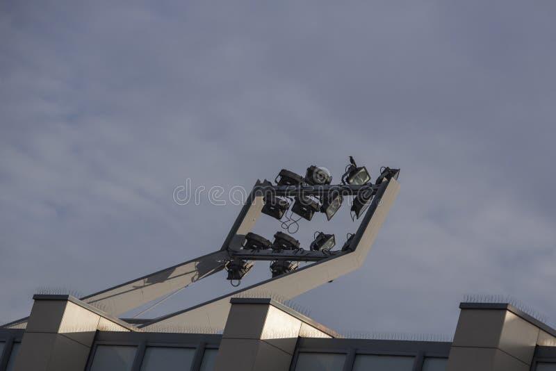 Les projecteurs mâtent au-dessus du stade de football photographie stock