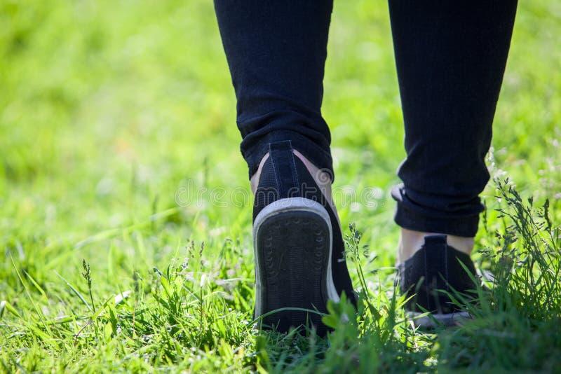 Les promenades d'homme le long de l'herbe dans les espadrilles en caoutchouc et le pantalon noir, se ferment vers le haut de la v photos stock