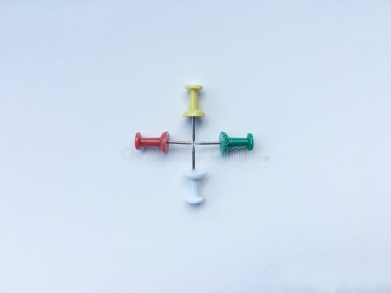 Les punaises colorées ont fait l'isolat croisé sur le fond blanc photos libres de droits