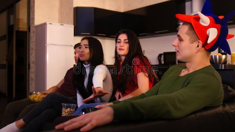 Les quatre jeunes s'asseyant sur le sofa et le match de football de observation Un homme jugeant la TV à distance et une femme es photographie stock libre de droits