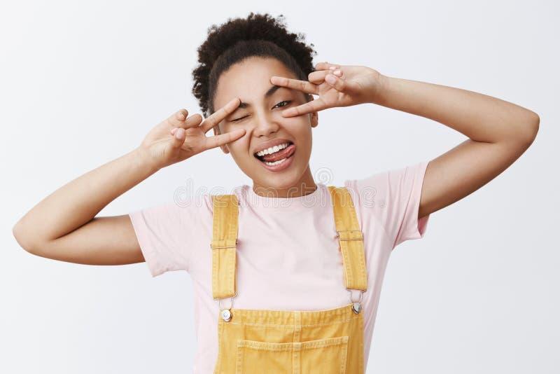 Les règles de haine vivantes comme veulent Jeune fille africaine aux cheveux bouclés heureuse et attirante insouciante avec l'app image libre de droits