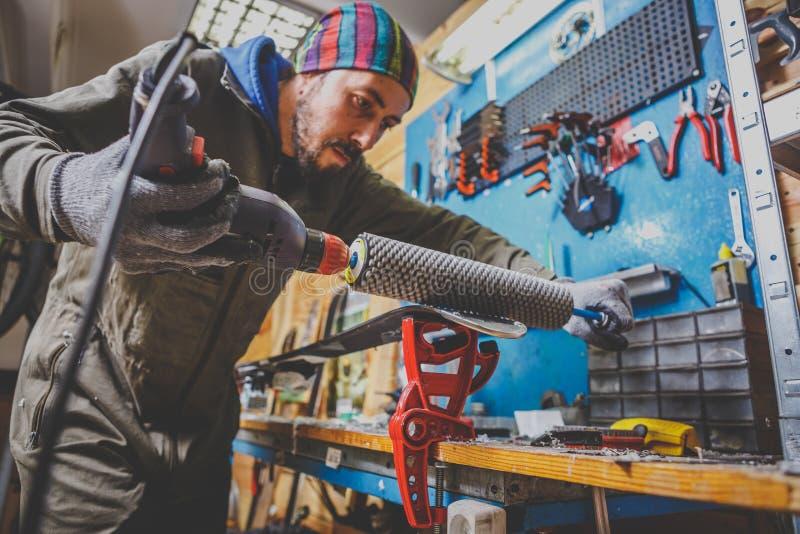 Les réparations d'un travailleur d'homme dans le ski entretiennent l'atelier la surface de glissement des skis, base polissant, p photos libres de droits