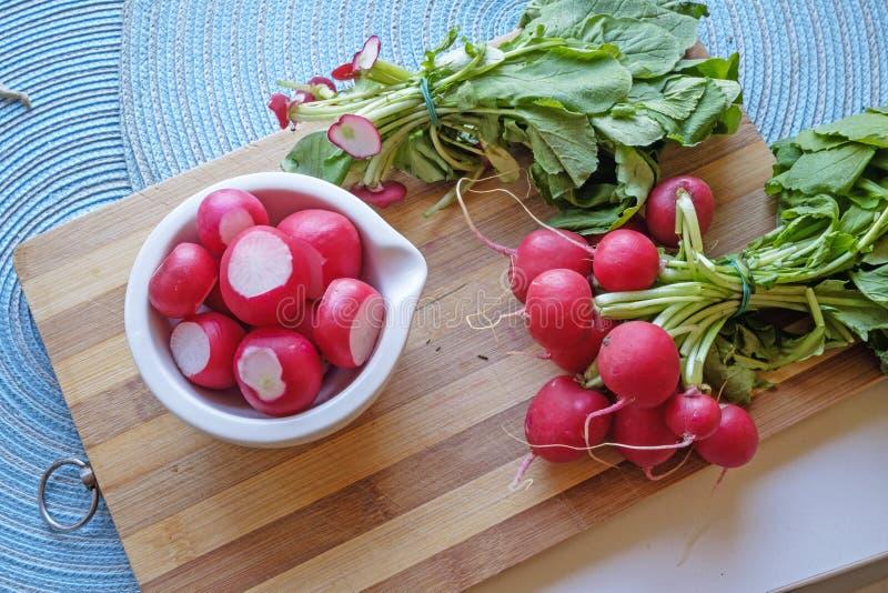 Les radis rouges dans une cuvette en céramique blanche aménagent large en parc supérieur image stock