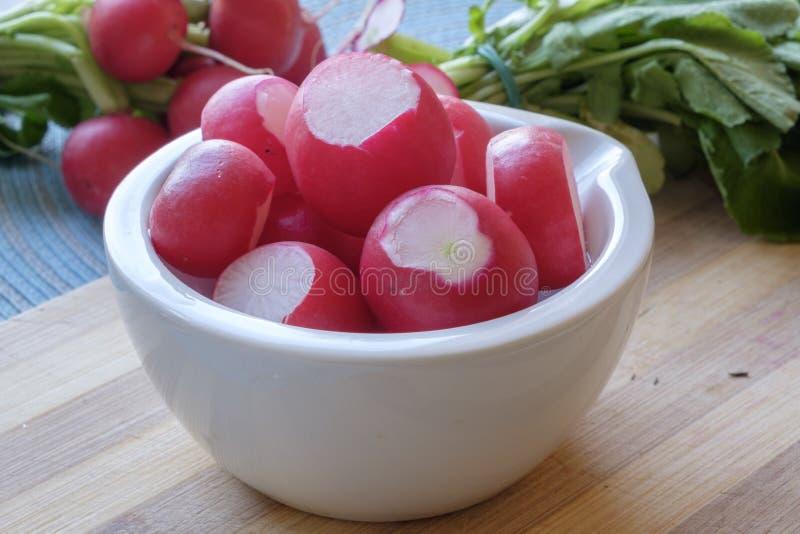 Les radis rouges dans une cuvette en céramique blanche aménagent serré en parc latéral image libre de droits