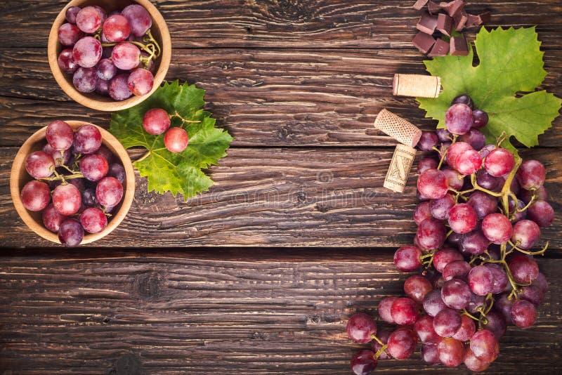 Les raisins se rassemblent avec des feuilles sur le fond en bois rustique Vue supérieure image libre de droits
