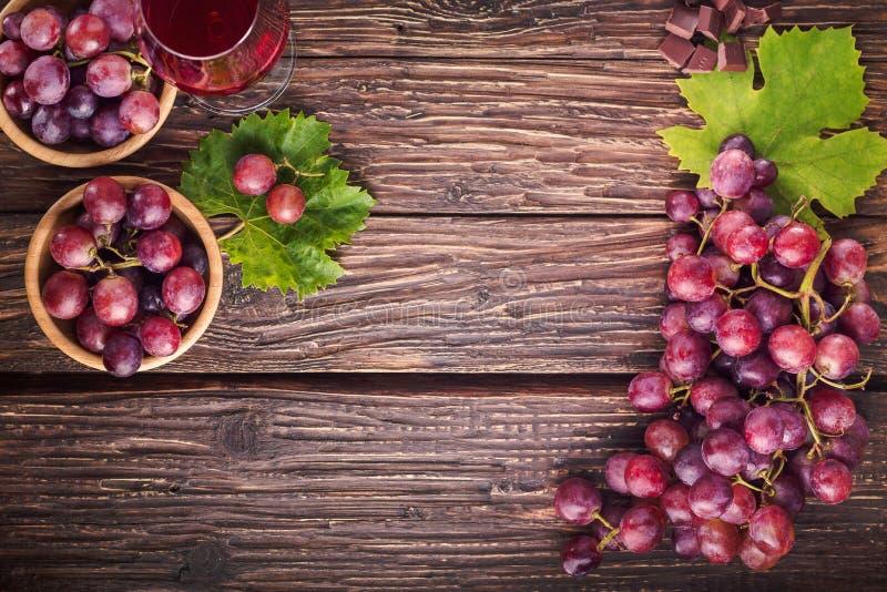 Les raisins se rassemblent avec les feuilles et le verre de vin sur un vieux dos en bois image libre de droits