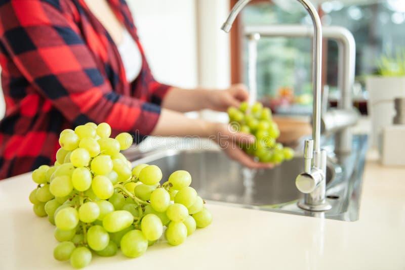 Les raisins verts sur le premier plan et une femme rince les raisins verts image stock