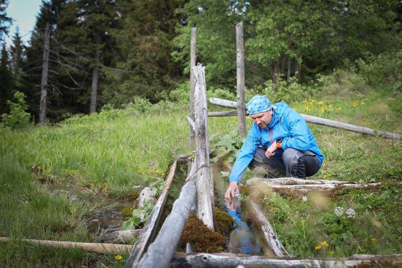 Les randonneurs équipent prendre l'eau claire du ruisselet dans la forêt photo libre de droits