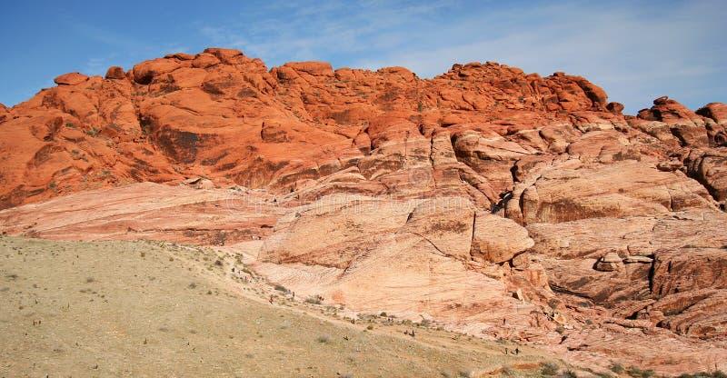 Les randonneurs et les grimpeurs ont rapetissé par la gorge rouge de roche photos libres de droits