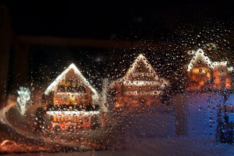 Les rangées de la maison de pain de gingembre de Noël derrière mouille le verre images stock
