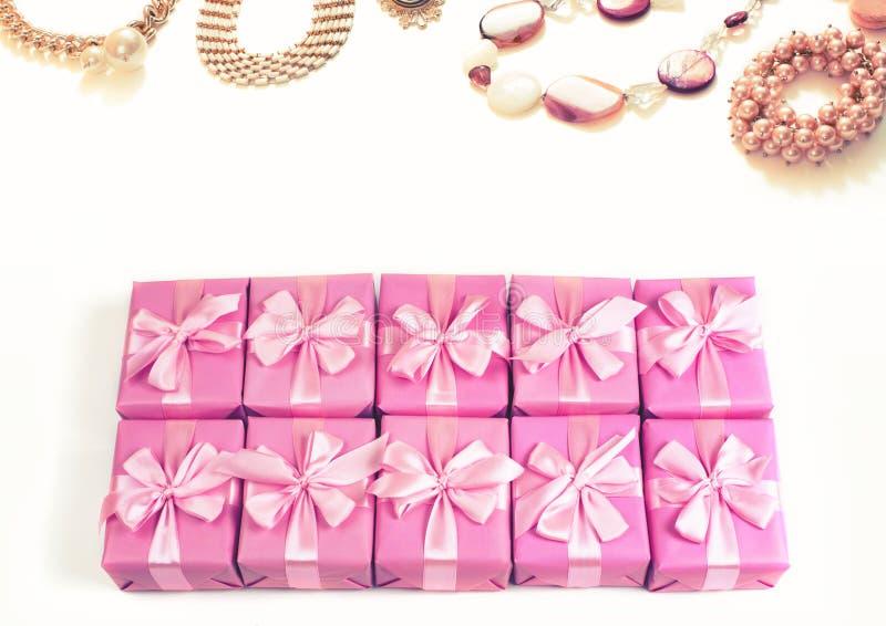 Les rangées des boîtes avec le satin de ruban de décoration de cadeaux cintrent les accessoires de mode roses pour la vue supérie photos libres de droits