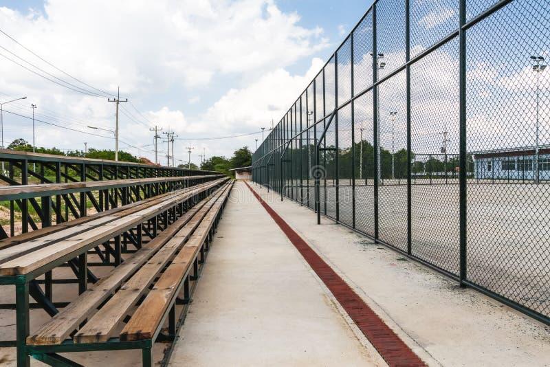Les rangées des sièges vides de tribune en bois du tennis mettent en place photographie stock