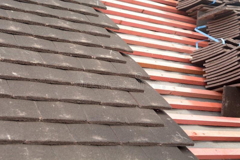 Les rangées des tuiles ont fixé aux lattes en bois sur le toit images stock