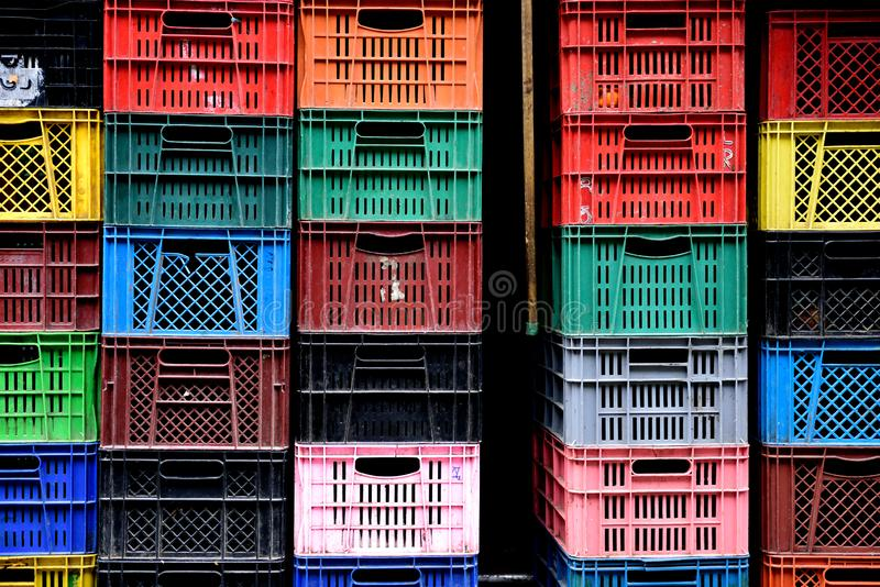 Les rangées et les piles de caisses en plastique colorées dans des agriculteurs produisent le marché photographie stock