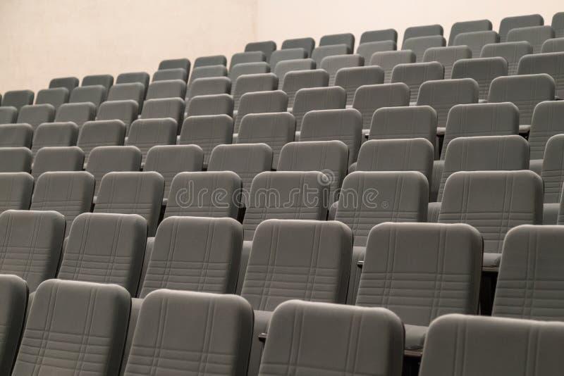 Les rangées vides du gris confortable pose le cinéma ou le théâtre images stock