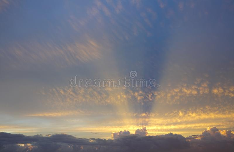 Les rayons d'or du soleil par derrière les nuages s'étendent à travers le ciel ci-dessus image stock