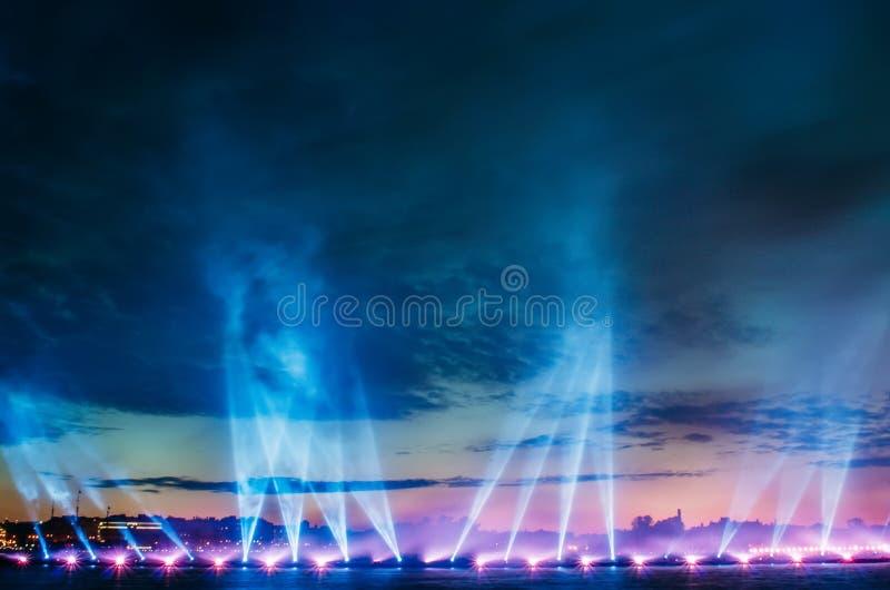 Les rayons de la lumière ont dirigé vers le haut du ciel la nuit dans la ville photo libre de droits