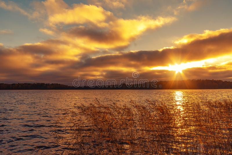 Les rayons de sun font leur voie par les nuages au-dessus du lac au coucher du soleil Beau fond égalisant de paysage images stock