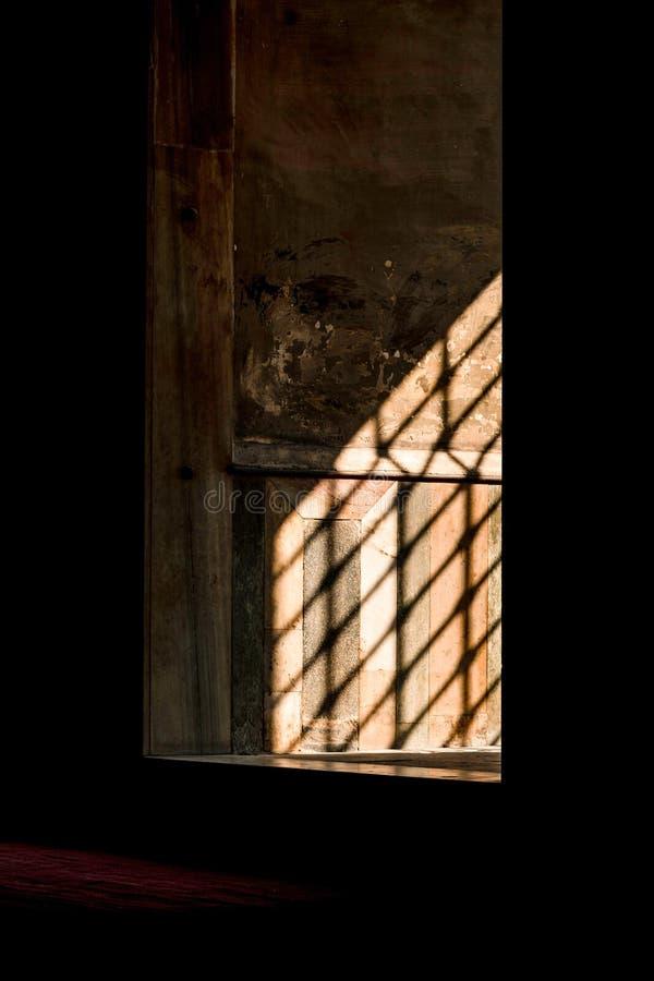 Les rayons de sun tombent dans la fenêtre par le trellis de fer dans la ville antique photos stock