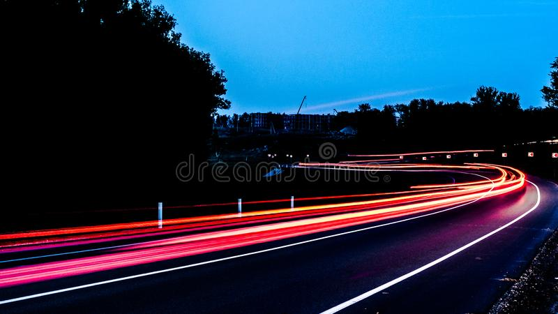 Les rayons rouges des voitures de lumière le trafic de nuit sur une route de campagne photos stock