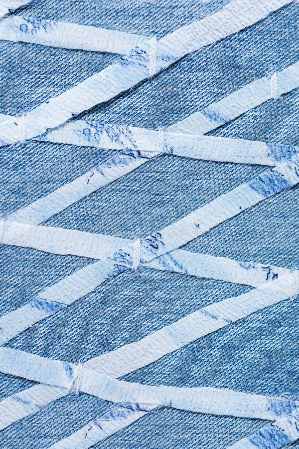 Les rayures minces cutted du tissu fin, cousu sur le denim bleu dans le modèle rhomboïde géométrique photo stock