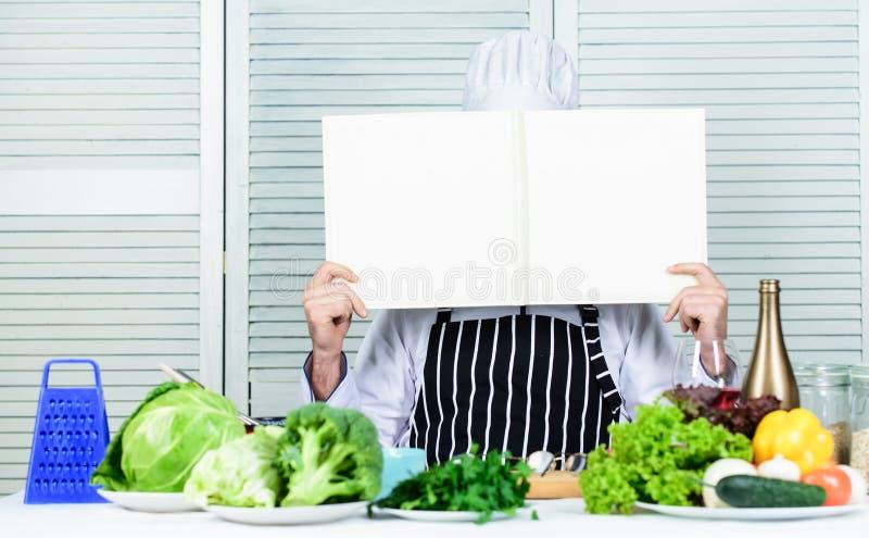 Les recettes de livre copient l'espace Le chef d'homme dans le chapeau et le tablier a lu le livre E r images stock