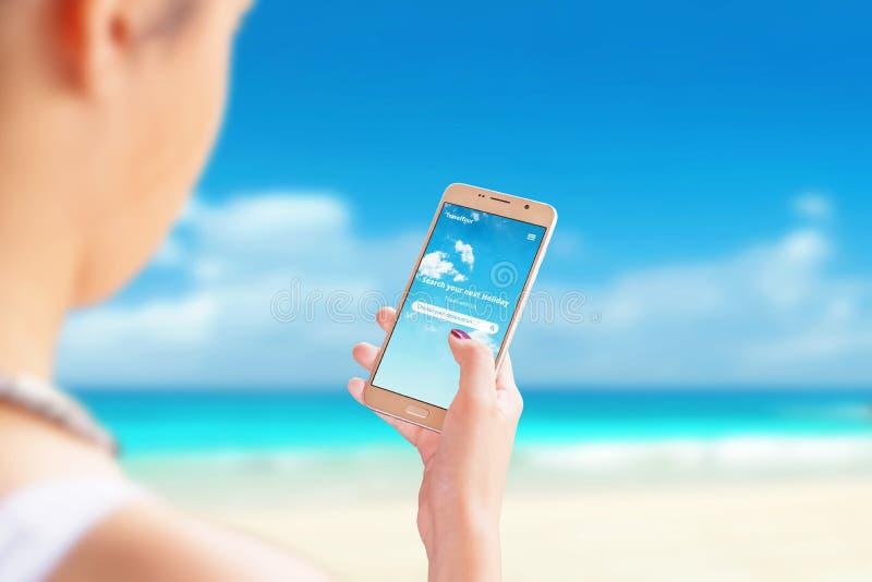 Les recherches de fille de nouvelles destinations pour le voyage et les vacances avec l'appli futé de téléphone sur la plage photographie stock libre de droits