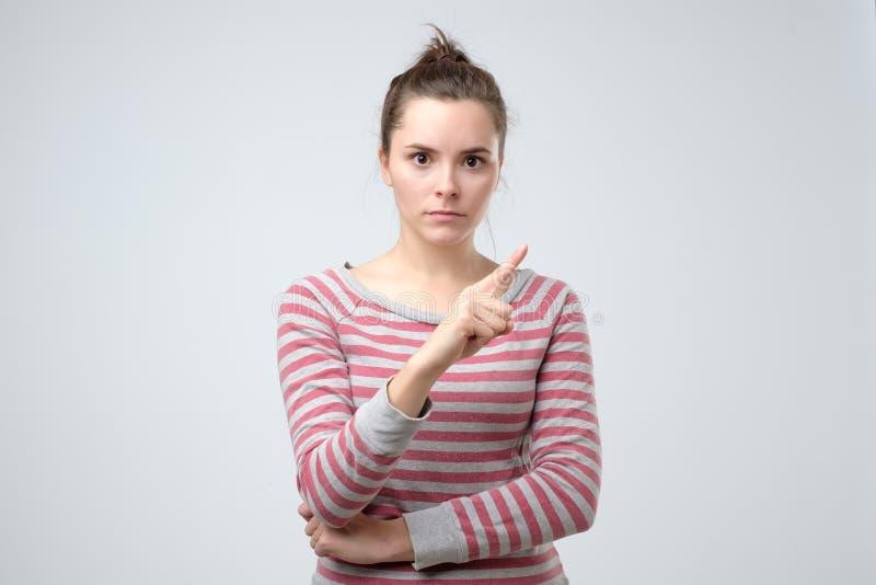 Les regards de jeune femme ont soumis à une contrainte et se dirigeant avec le doigt n'indiquant non photos libres de droits