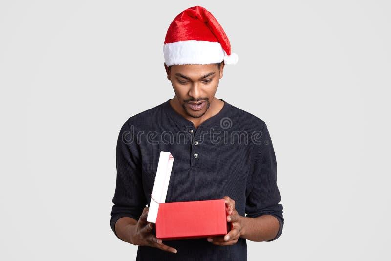 Les regards masculins noirs étonnés avec le choc au boîte-cadeau, voit le présent cher, porte la boîte, utilise le chapeau de San images stock