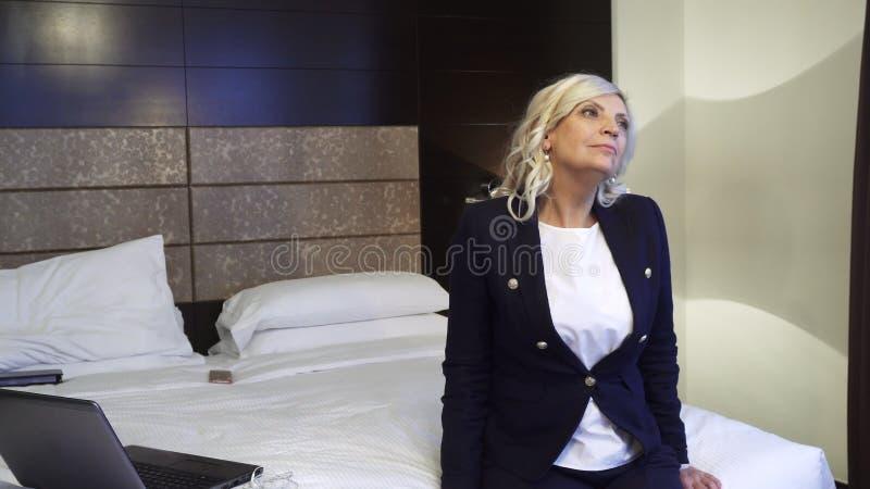 Les repos fatigués de femme sur le lit après un ` s de dure journée fonctionnent photos stock