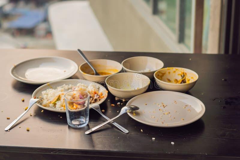 Les restes de la nourriture dans des plats, miettes sur la table après le déjeuner o photo libre de droits