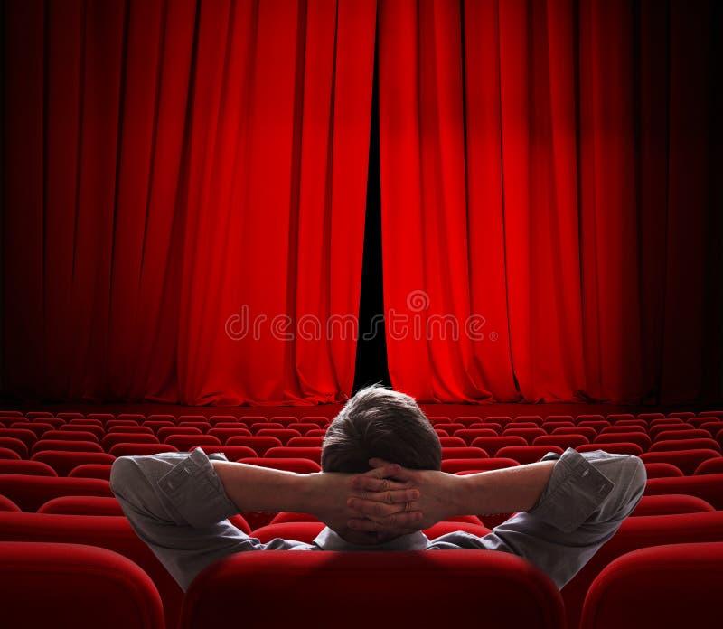Les rideaux rouges en écran de cinéma s'ouvrent légèrement pour le VIP images libres de droits