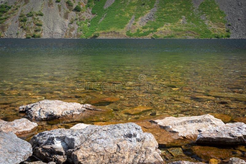 Les roches dans l'eau clair comme de l'eau de roche de Wast arrosent le lac dans le lac Dist photographie stock libre de droits