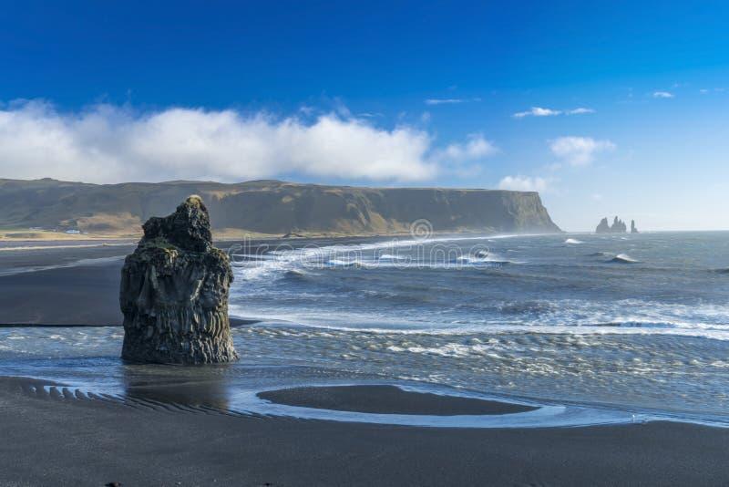 Les roches et les clifs sur Kirkjufjara noircissent la plage de sable, Islande du sud image stock