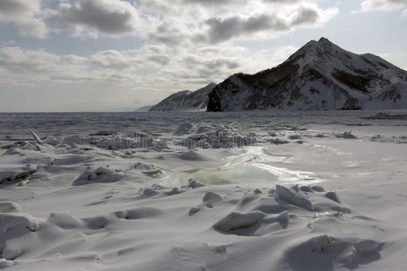 Les roches le long du rivage d'une mer congelée images libres de droits