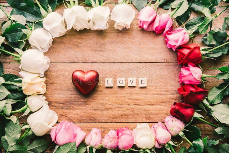 Les roses colorées ont aligné sur un plancher en bois avec le coeur et le mot et le x22 ; L photos stock