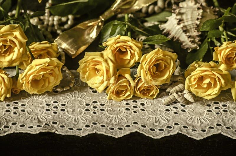 Les roses jaunes, les branches sèches du gypsophila blanc, roseaux à la frontière blanche de dentelle avec des perles perle sur l photos stock