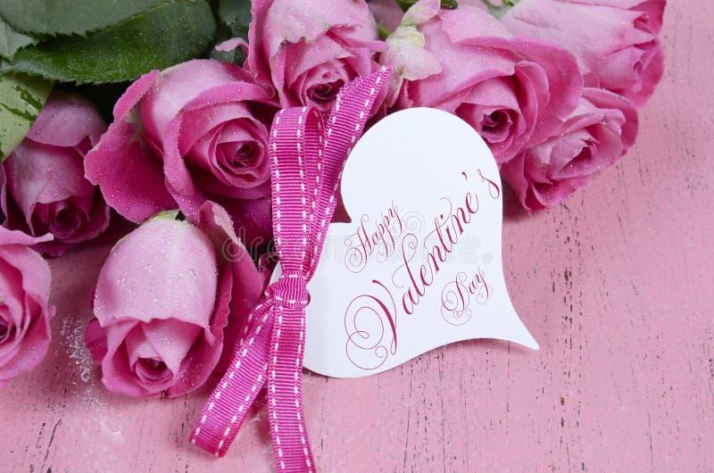 Les roses roses avec le coeur heureux de jour de valentines forment l'étiquette de cadeau image libre de droits