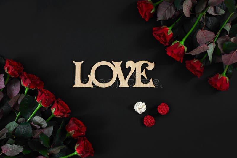 Les roses rouges fleurit avec le mot en bois AMOUR sur le fond noir avec photo stock