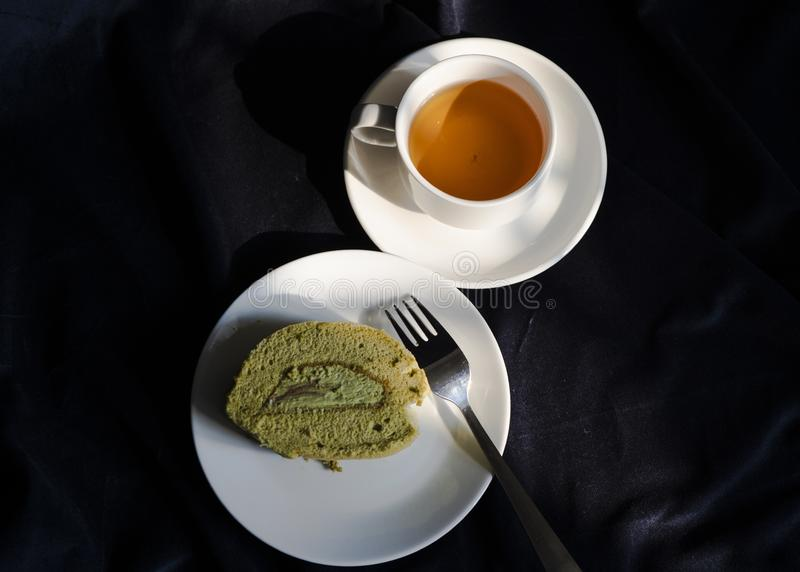 Les rouleaux délicieux de gâteau de matcha et une tasse de thé vert images stock