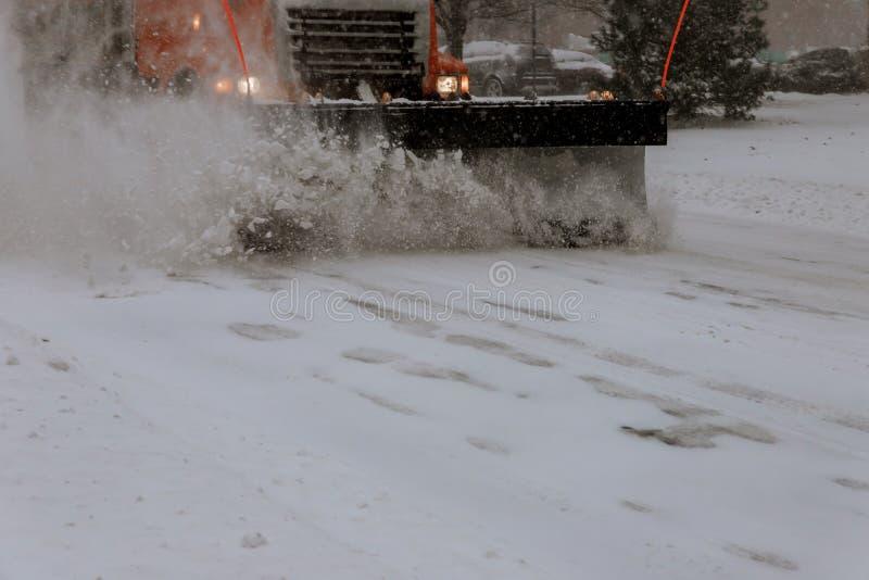 Les rues de ville de nettoyage de camion de solvant de neige dans la neige fulminent photo libre de droits