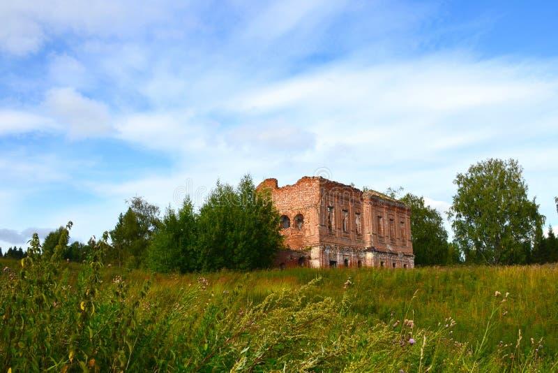 Les ruines d'une vieille forteresse ruinée de brique rouge dans les bosquets de la hauts herbe et arbres photo libre de droits