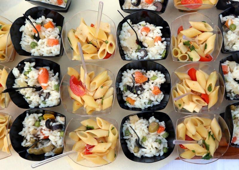 Les salades froides de riz et de pâtes dans de petites cuvettes en plastique, préparent pour une partie d'été image stock