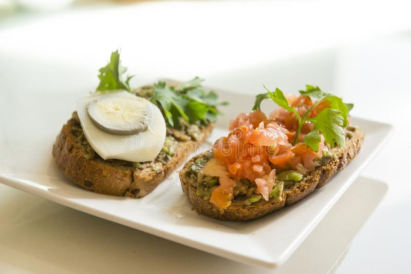 Les sandwichs avec l'avocat, la tomate, l'oeuf et le persil verts, appetize photo stock