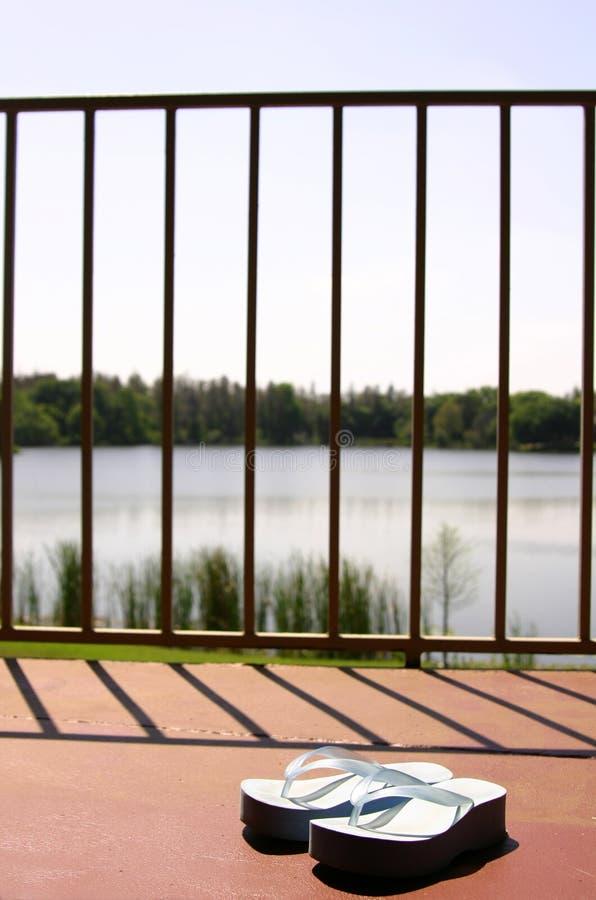 Les santals sur le patio d'un lac affrontent l'appartement images stock